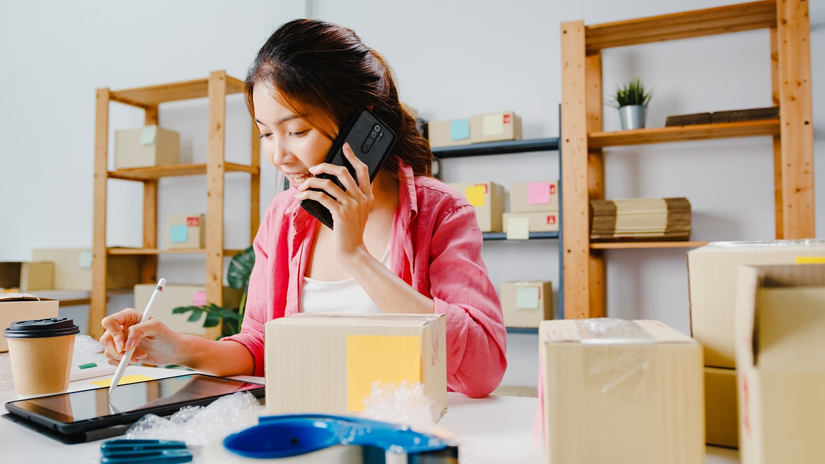 young-asia-businesswoman-using-mobile-phone-call-receiving-purchase-order-check-product-stock-work-home-office-small-business-owner-online-market-delivery-lifestyle-freelance-concept