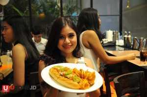 Hooters Girl memperlihatkan salah satu menu di restoran / © Ari Setiyawan